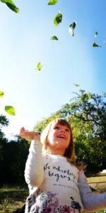 Copil de grădiniță jucându-se cu frunze